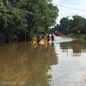Rescuers assisted two victims from a  a vehicle that had entered high waters on the roadway.