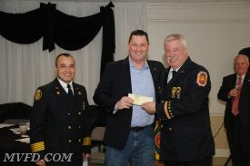Clarke Guy of the Mechanicsville Optimist Club presents a check to Chief Trowbridge and President Montgomery.