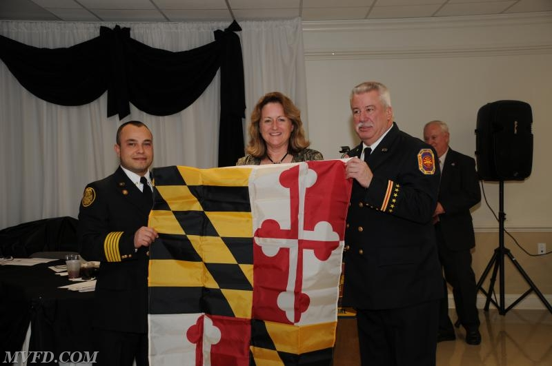 Delegate Deb Ray presents Chief Trowbridge and President Montgomery with the Maryland Flag.