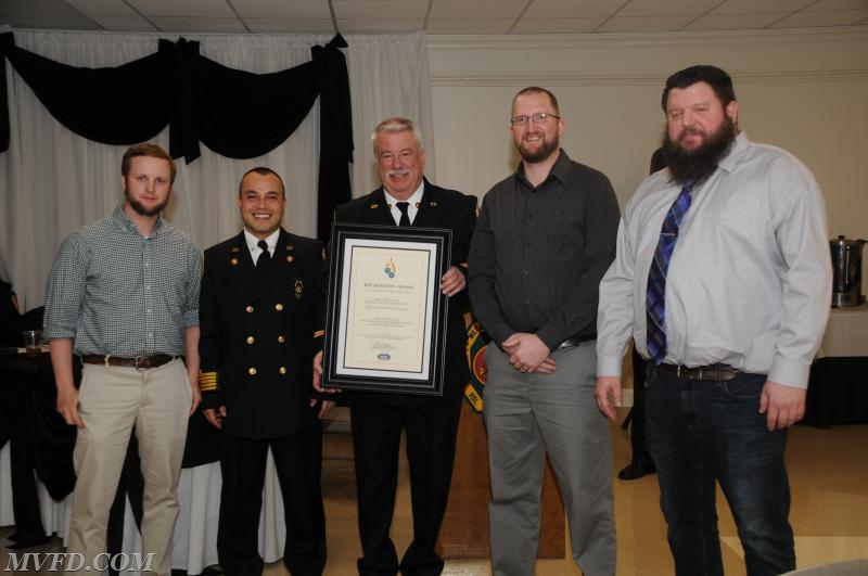 Evan Gray, Gary Campbell and Josh Noppenberger from Manns Woodward Studios presents Chief Trowbridge and President Montgomery a plaque for the station.