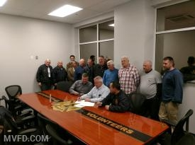 Our Apparatus Salesman Randy, President Montgomery, and Fire Chief Trowbridge signing the contract while the Board of Directors oversee.