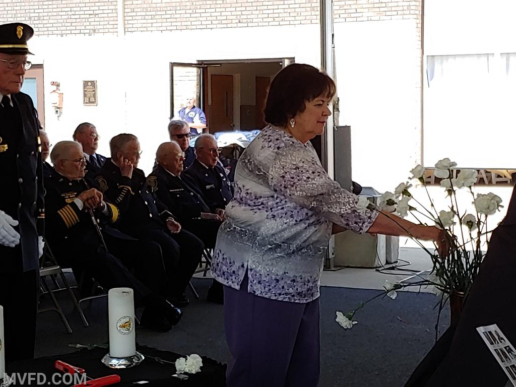 Catherine Fowler places the flower in the boot in remembrance of her husband and former member Tucker Fowler.