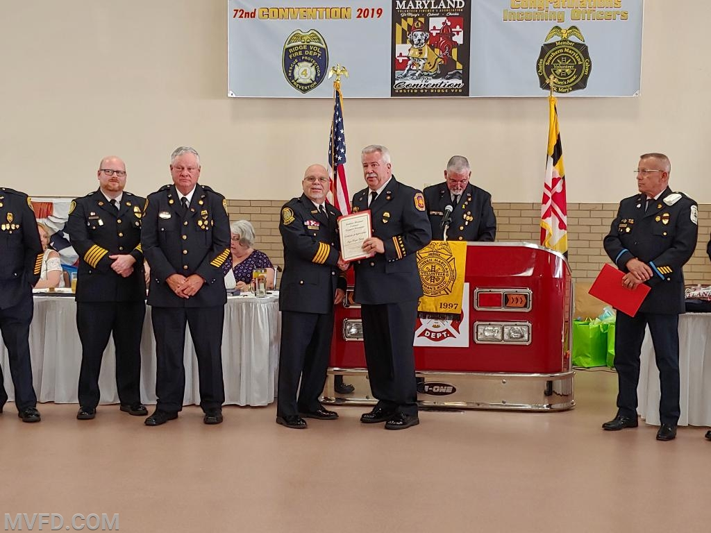 President John Montgomery accepting 50 year certificate and pin on behalf of Wayne Copsey.