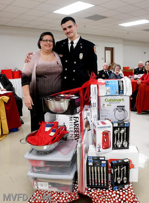 Auxiliary President Cindy Turner presenting Jake Senatore with kitchenware for the members kitchen