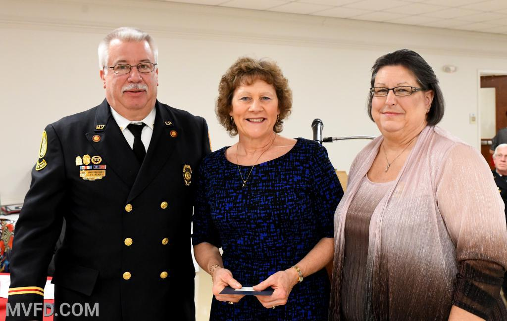 "President John ""Monkey"" Montgomery along with Auxiliary President Cindy Turner presenting Natalie Olson with a thank you gift for donating flowers for the banquet"